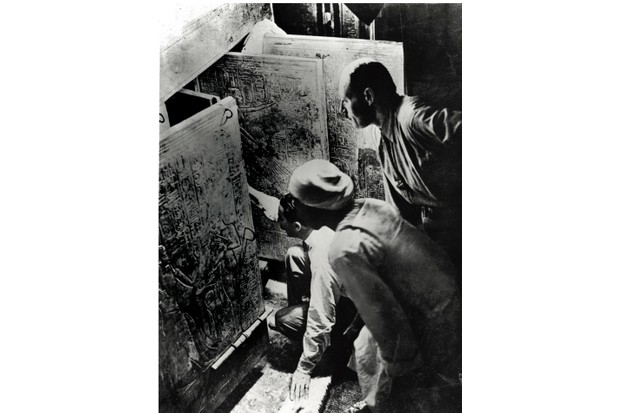Carter, watched by assistant Arthur Callender and an Egyptian foreman, opens the golden shrines surrounding the sarcophagus. (Hulton Archive/Getty Images)
