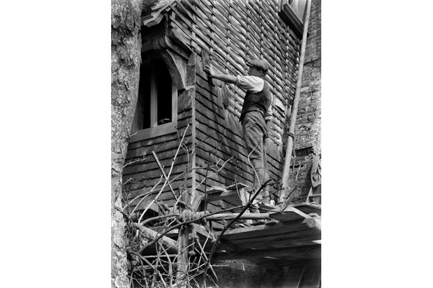 view showing the exterior walls of an unidentified house being rehung with tiles 1920 - 1930