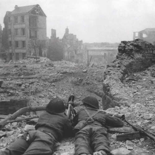 The Norman town of Caen, which fell British and Canadian troops on July 9, had been heavily mined by the Germans, and parts of it were badly damaged in the battle which led to its capture. Enemy snipers gave a lot of trouble and caused numerous casualties in the streets before they were all ejected from their hiding places and rounded up by British and Canadian patrols. A British sniper watches for enemy movement through his telescopic sights in Caen on July 19, 1944. (AP Photo/British Official Photo)
