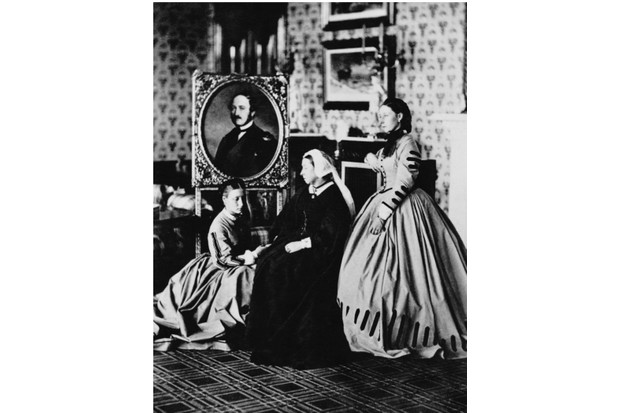 1863: Queen Victoria at Balmoral with her daughters, Princess Alice (wife of Duke Louis IV of Hesse) and Princess Louise, Duchess of Argyll, and a portrait of her late husband, Prince Albert. (Photo by Hulton Archive/Getty Images)