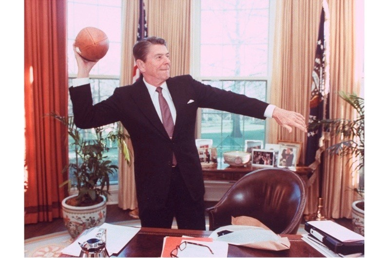 President Ronald Reagan throwing a football from his desk in the Oval Office. (Photo by Mary Anne Fackelman-Miner/White House/The LIFE Picture Collection/Getty Images)