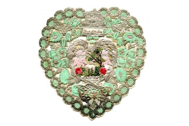 A Valentine's day card showing an embroidered green heart and scenery including a dog.