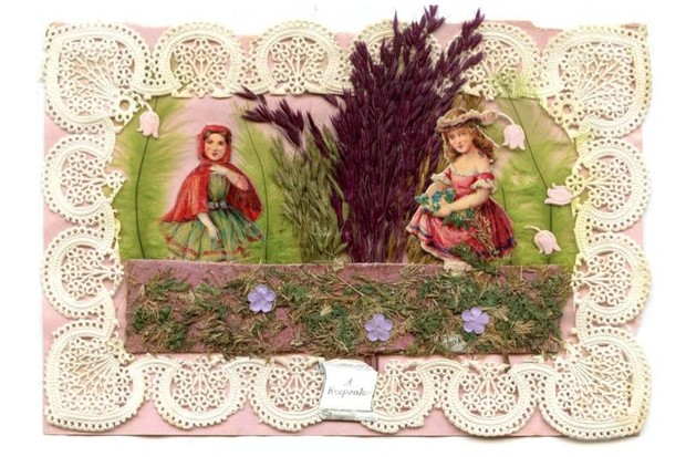 A Valentine's day card showing two young women complete with decorative pressed grass and scraps of lace.