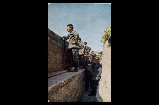 A man looks over the top of a trench during World War One