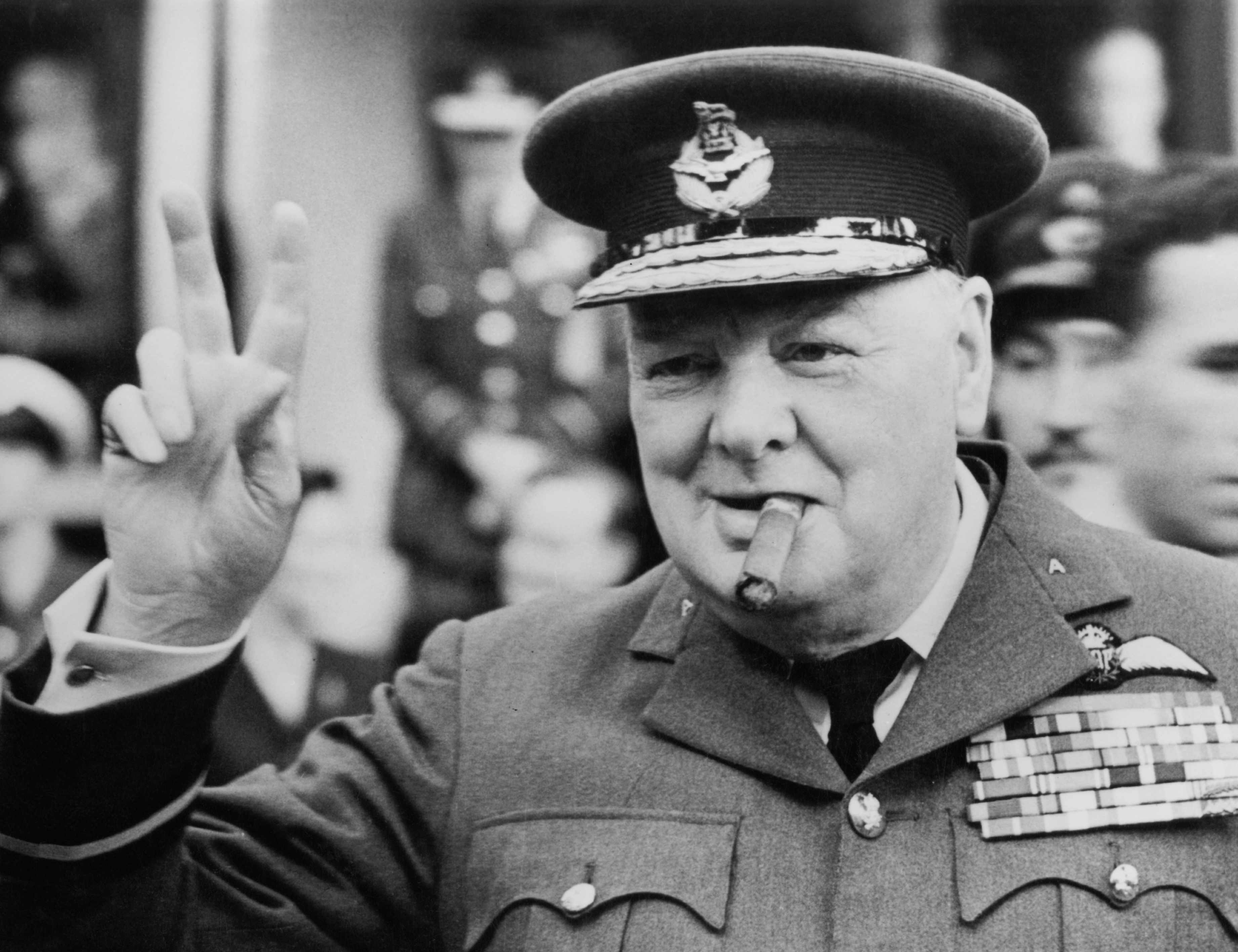 Winston Churchill gives his famous v-sign as he opens the new headquarters of 615 (County of Surrey) Squadron of the RAAF (Royal Auxiliary Air Force) at Croydon, 1948. (Photo by Central Press/Hulton Archive/Getty Images)