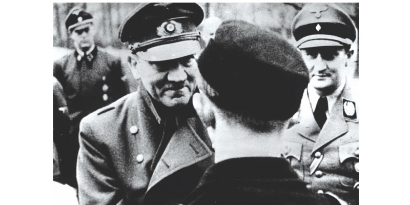 In his last official photo, Adolf Hitler (1889 - 1945) leaves the safety of his bunker to award decorations to members of Hitler Youth.   (Photo by Keystone Features/Getty Images)