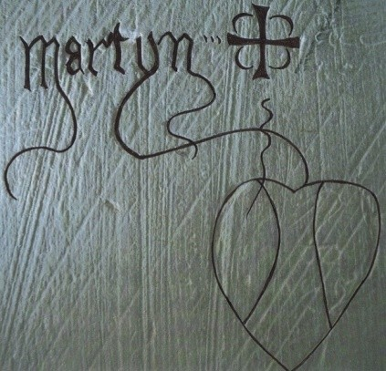 The name 'Martyn', a cross and a heart, graffiti in a medieval church