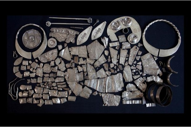 A large collection of Pictish silver artefacts laid out on a black background.