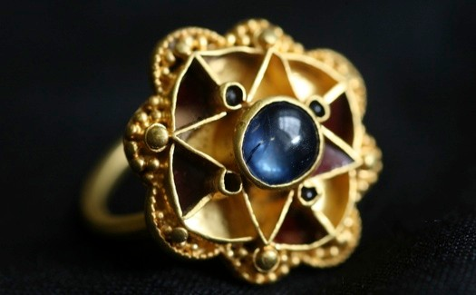 A Unique Sapphire Ring, found near York, has been acquired by The Yorkshire Museum for £35,000. The ring which measures around 2.5cm across, is intricately made of gold, prestige glass and a large sapphire. This is only the second known use of a sapphire in jewellery found in the country, the first being a 5th century Roman example. The ring was probably worn by someone of very high status, such as a king, queen or chief. But from which period remains unclear. The use of a sapphire would have been common for kings in the medieval period, but the gold beading would suggest the Viking period (10th-11th centuries). However the use of gold and red glass is more typical of the 7th-9th centuries Anglican style - this mix of materials and styles thus makes it a unique find. It was found by metal detectorist Michael Greenhorn from York in 2009, and will now go on show at The Yorkshire Museum in York, in the next few weeks. For Further Info: YMT Press Office/Lee Clark +44(0)1904 687673