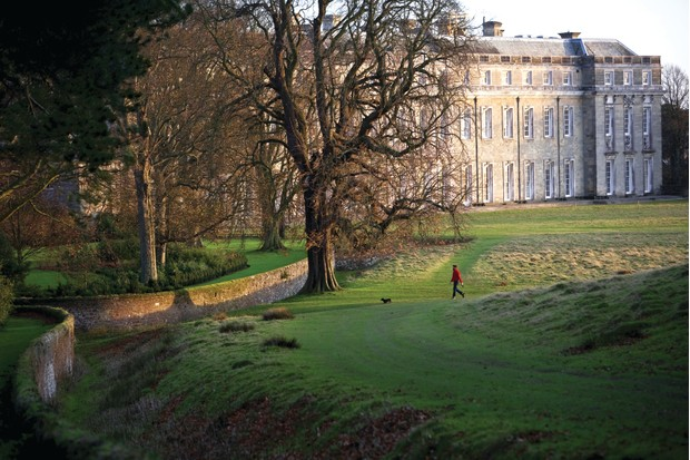 Visitor walking by the west front of Petworth House and the ha-ha in the grounds in November, West Sussex. The west front was entirely rebuilt between c.1688 and 1702.