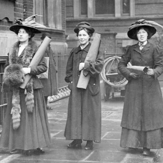 Three suffragettes prepare to chain themselves to the railings, 1909