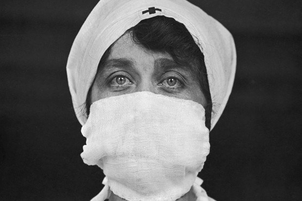 A Red Cross worker in the United States wears a mask to reduce the risk of contracting or spreading the disease in 1918. Though doctors didn't initially understand the nature of the infectious agent, 'social distancing' helped slow the propagation of the flu. (Photo by Paul Thompson/FPG/Hulton Archive/Getty Images)