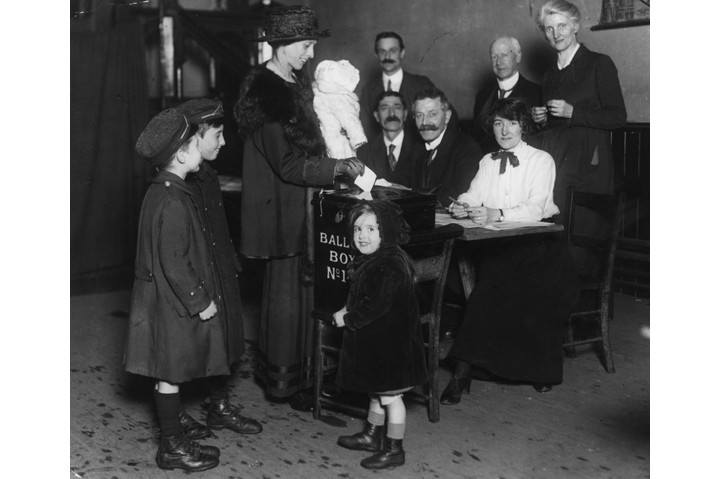 "A woman casts her vote, accompanied by her children, in December 1918. Women weren't as ""timid and uncertain at the polling stations as had generally been anticipated"", reported 'The Times'. (Photo by Topical Press Agency/Getty Images)"