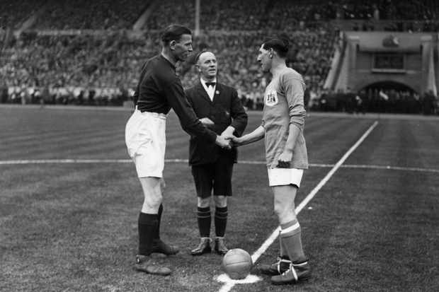 A Cardiff City player shakes hands with an Arsenal player before the kick off of the 1927 FA Cup final. (Photo by H. F. Davis/Topical Press Agency/Getty Images)