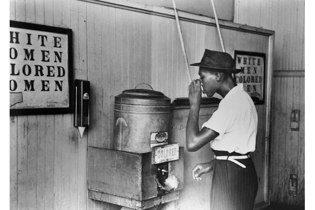 King was born in 1929, into the degrading conditions of racial segregation, often known as Jim Crow. Here, a man drinks from a segregated water fountain in Oklahoma City. (Photo by Bettmann/Getty Images)