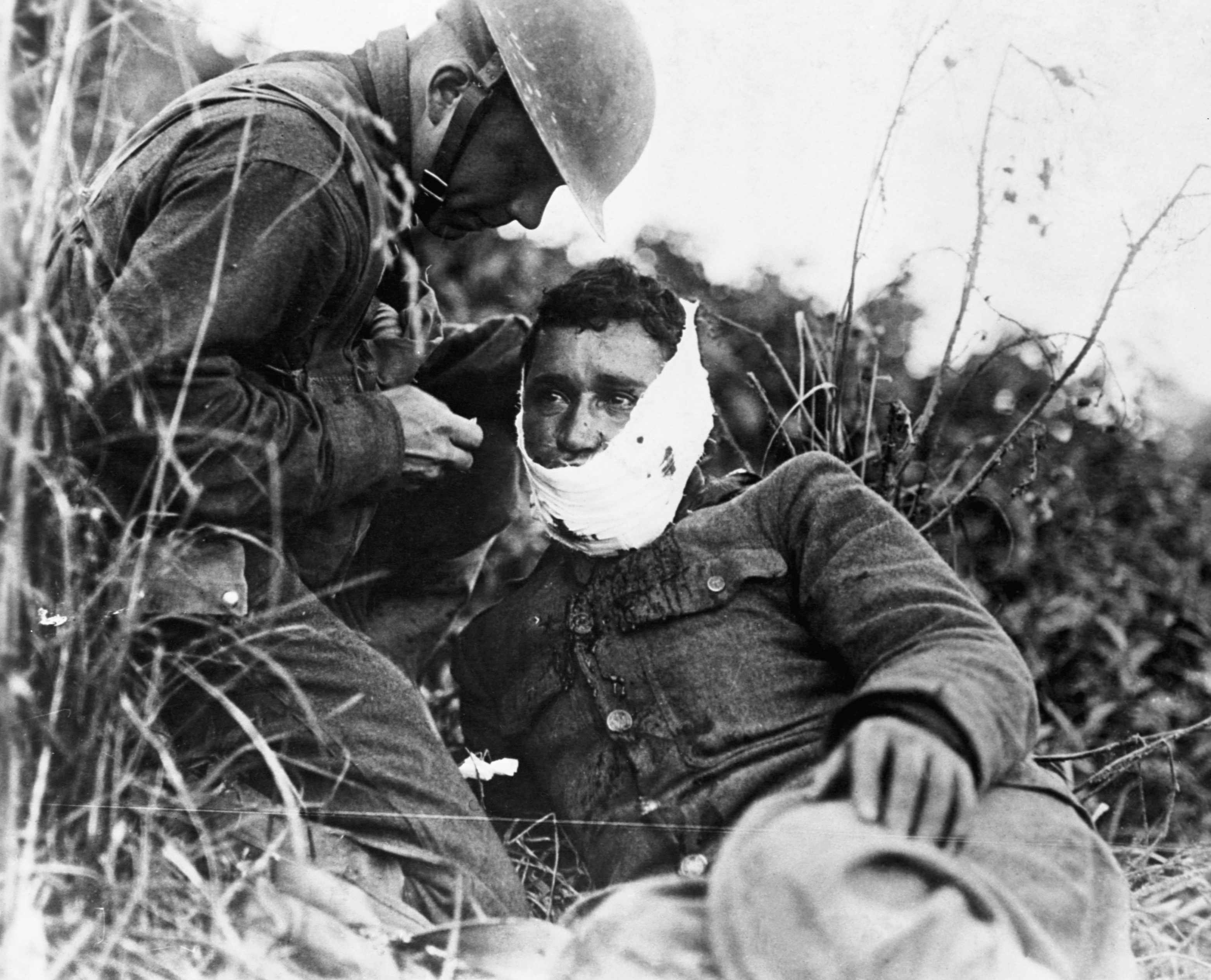 A wounded soldier of Company K, 110th Regiment Infantry, receives first-aid treatment from a comrade in Varennes-en-Argonne, France, 26 September 1918. (Photo by Corbis via Getty Images)