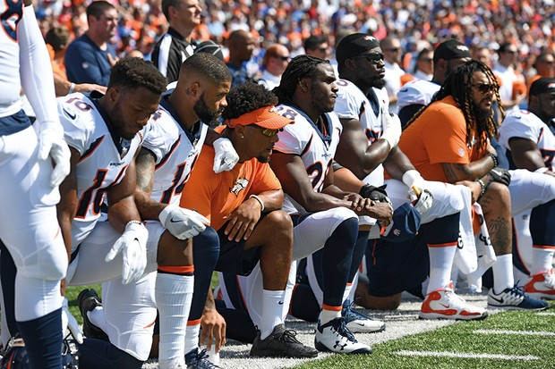 Players of the Denver Broncos American football team kneel during the US national anthem