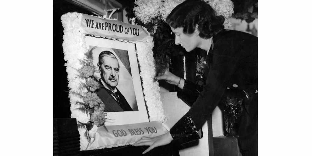 A woman at a floral tribute to Neville Chamberlain at a florist in Ludgate Circus, London, 1938. In the wake of the Munich agreement, the prime minister was understood to be a hero of women everywhere. (Photo by Harry Todd/Getty Images)