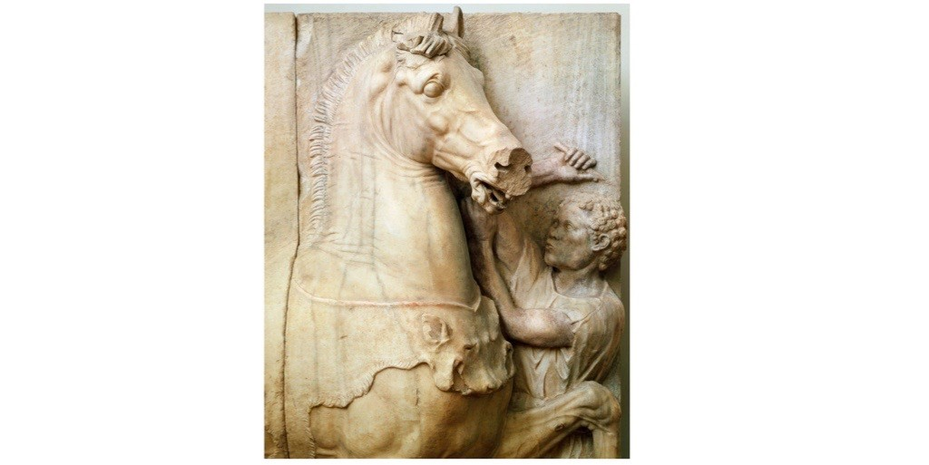 A detail of a funerary monument from Athens, Greece depicting a squire taming a horse. Holding elaborate funerals was one of the many ways in which aristocrats broadcast their great wealth. (Photo By DEA/G.DAGLI ORTI/De Agostini/Getty Images)
