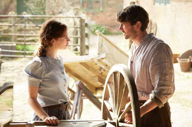 Actress Lily James and actor Michael Huisman looking at each other in a still from the film The Guernsey Literary and Potato Peel Pie Society