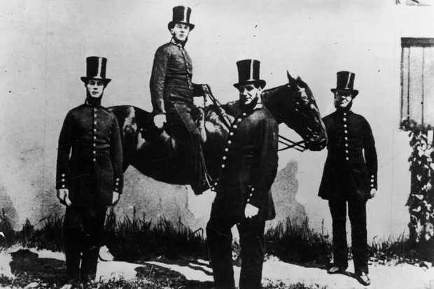 Four police officers, members of the Bow Street Horse Patrol, pose for a photograph with a horse.