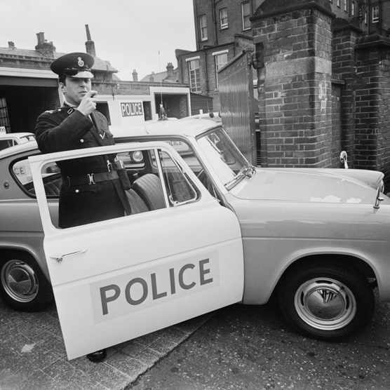 A police officer with a new Ford Anglia 105E patrol car, 1 March 1967. The cars are intended for use by single-man crews. (Photo by Harry Dempster/Daily Express/Hulton Archive/Getty Images)