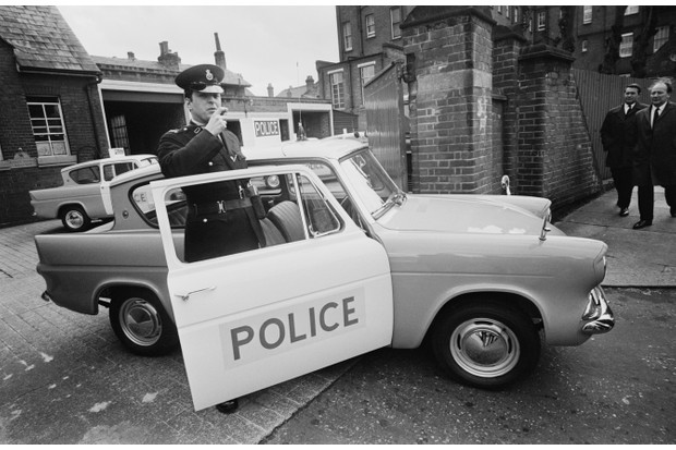 A black and white photograph showing a police officer with a new Ford Anglia 105E patrol car.