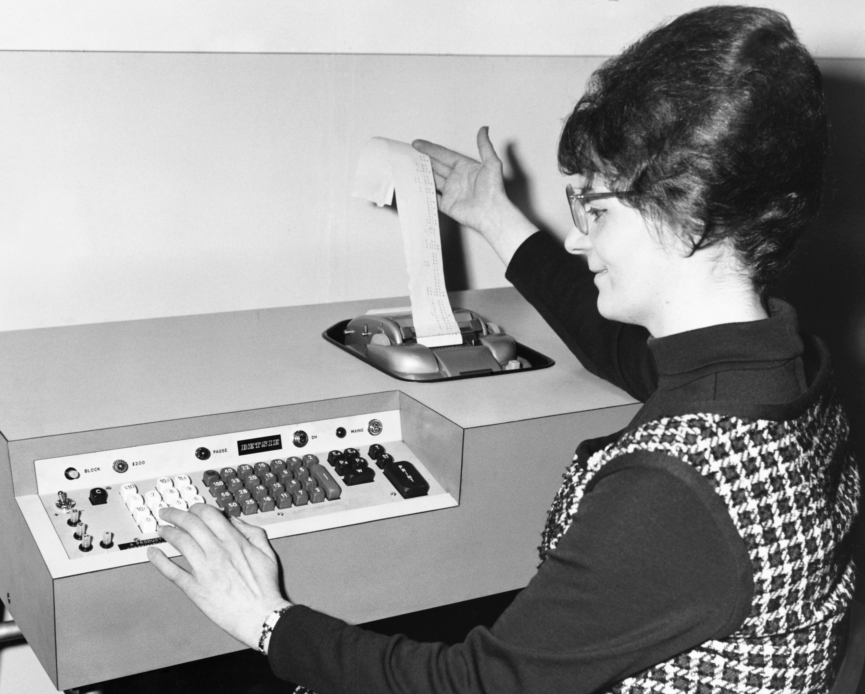A female computer programmer demonstrates a new computer in the 1960s.