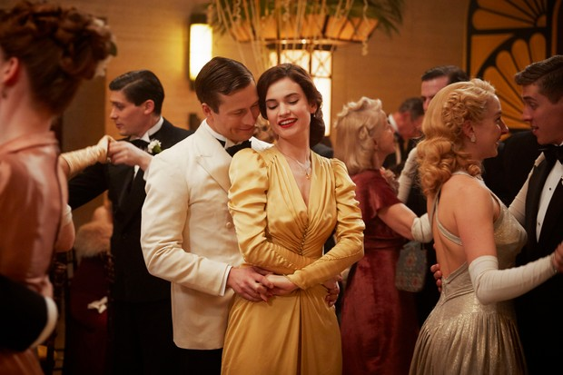 A still from the film The Guernsey Literary and Potato Peel Pie Society showing a man and woman dancing at a formal event