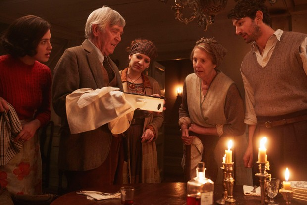 A still from the film The Guernsey Literary and Potato Peel Pie Society showing a group of people looking at a pie