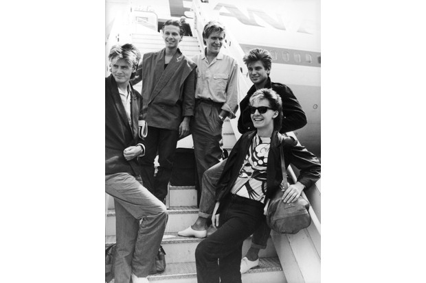Members of the British pop group Duran Duran pose on an airplane ramp before departing for Australia from Heathrow Airport, 26 July 1983. (Photo by Express Newspapers/Getty Images)