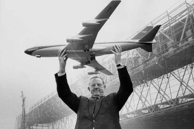 Keith Granville, managing director of BOAC (British Overseas Airways Corporation), holding a model of the Boeing 747 jet, with the new aircraft hangars under construction in the background, at Heathrow Airport, 17 March 1969. (Photo by Jim Gray/Keystone/Getty Images)