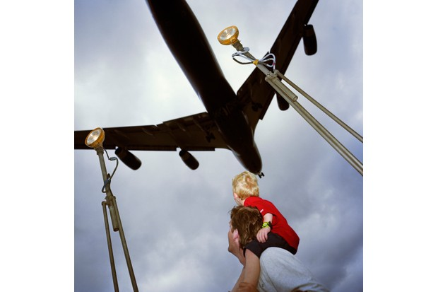 A father supports his son on his shoulders as a four-engined airliner passes directly overhead, about to land at London's Heathrow airport, 17 August 1997. Prior to the 9/11 terrorist attacks in New York, British airport authorities and police tolerated plane spotters near runway fences. (Photo by In Pictures Ltd./Corbis via Getty Images)