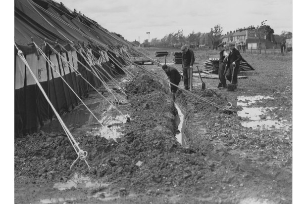 Workmen attempt to trench away water from around the marquees for passengers at the new London Airport, 30 May 1946. The marquees were a temporary arrangement as the airport prepared to accommodate flights from the United States. (Photo by Fox Photos/Hulton Archive/Getty Images)