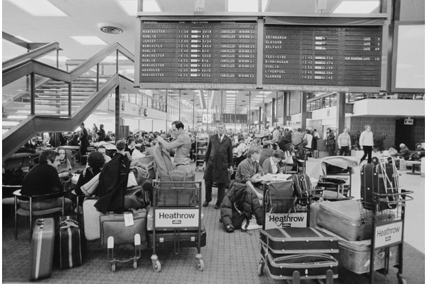 Passengers wait near the departures board at Heathrow Airport, 4 January 1979. (Photo by John Minihan/Evening Standard/Hulton Archive/Getty Images)