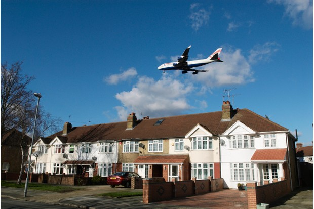 An aeroplane flying over rooftops near Heathrow Airport, April 2008. (Photo by BuildPix/Construction Photography/Avalon/Getty Images)