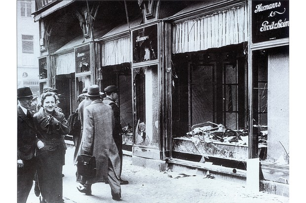 Pedestrians pass the broken windows of a Jewish-owned shop in Berlin after the attacks of Kristallnacht in November 1938. The brutal events spurred the British government to offer aid to Jewish refugees. (Photo by Universal History Archive/Getty Images)