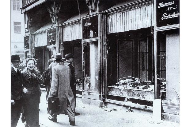 Os pedestres passam pelas janelas quebradas de uma loja de propriedade judaica em Berlim depois dos ataques da Kristallnacht em novembro de 1938. Os eventos brutais estimularam o governo britânico a oferecer ajuda aos refugiados judeus.  (Foto do Arquivo da História Universal / Getty Images)