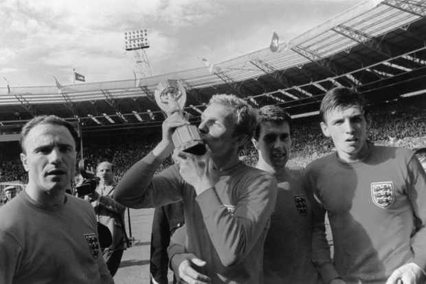 England's World Cup-winning captain, Bobby Moore (1941–93) kisses the Jules Rimet World Cup trophy after England's 4-2 win over West Germany in the 1966 World Cup final at Wembley Stadium, London. Also pictured are Moore's team-mates George Cohen, Geoff Hurst and Martin Peters. (Photo by Fox Photos/Getty Images)