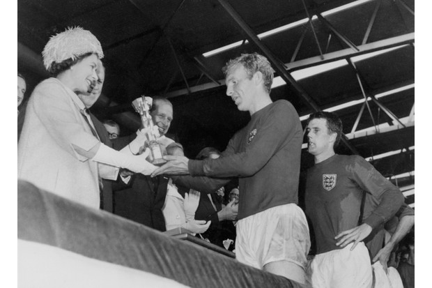 Queen Elizabeth II presents the Jules Rimet Cup to Bobby Moore, captain of England's national football team, as her husband Prince Philip and hat-trick scoring forward Geoff Hurst (right) look on. (Photo by STAFF/AFP/Getty Images)