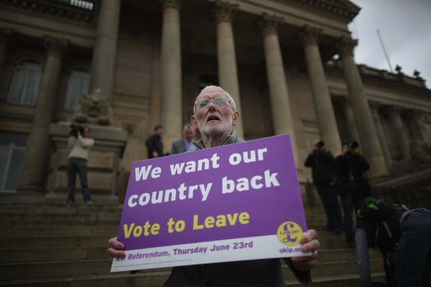 A Vote to Leave campaigner holds a placard as the then-leader of the United Kingdom Independence Party (UKIP), Nigel Farage, campaigned for votes to leave the European Union in the 2016 referendum, 25 May 2016 in Bolton. Britain voted to leave the EU on 23 June 2016. (Photo by Christopher Furlong/Getty Images)