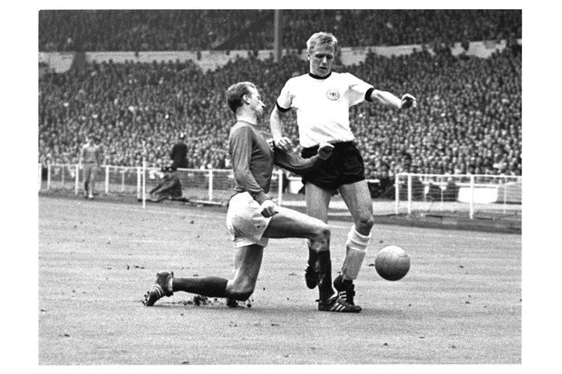 The West Germany team opened the scoring after just 12 minutes, only for England's replacement striker Geoff Hurst to equalise four minutes later. With 12 minutes of regular time remaining, England's midfielder Martin Peters scored another goal, bringing the score to 2–1. Here, England's Jackie Charlton rushes in to tackle West Germany's forward Sigfried Held. (Photo by Hulton-Deutsch/Hulton Deutsch/Corbis/VCG via Getty Images)