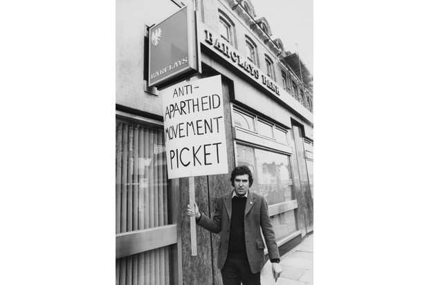 British activist and politician Peter Hain leads an anti-apartheid demonstration outside Barclays Bank in Richmond Road, Putney, London, 20th January 1977. He is protesting the funding of the South African armed forces by the South African subsidiary of Barclays. Hain was accused of robbing the same branch of Barclays in 1974, but acquitted. (Photo by Gary Weaser/Keystone/Hulton Archive/Getty Images)