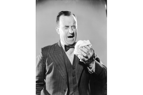 A man sneezes into a handkerchief, c1936. (Photo by Fox Photos/Getty Images)