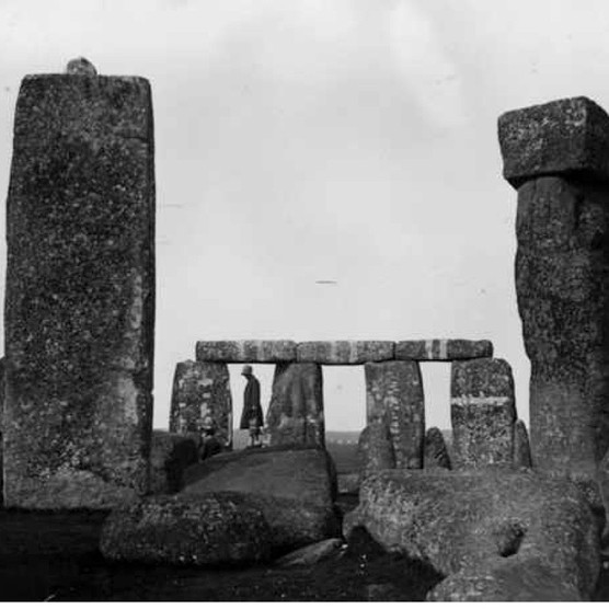 A visitor stands on a toppled standing stone at the megalithic structure of Stonehenge on Salisbury Plain. (Photo by General Photographic Agency/Getty Images)