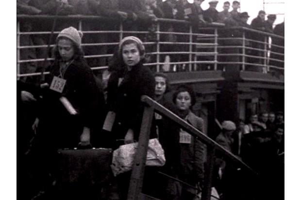 Lore Segal, de 10 anos, usa uma etiqueta com o número 152. A foto foi tirada em sua chegada a Harwich, Essex, em um dos Kindertransports em 1938. (Foto usada por cortesia de Lore Segal)
