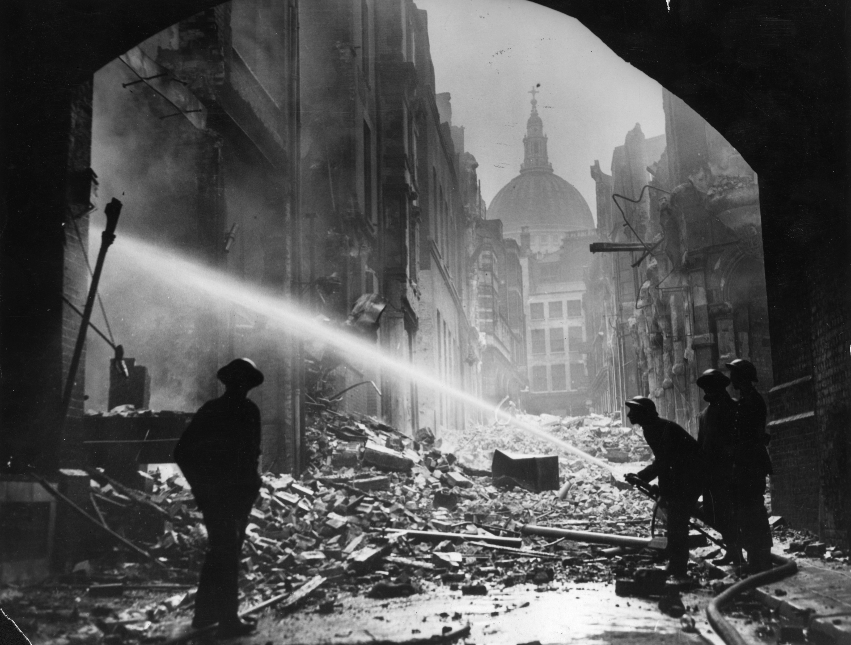 Firemen tackle a blitz fire amidst the rubble surrounding St Paul's Cathedral, London. (Photo by Fox Photos/Getty Images)