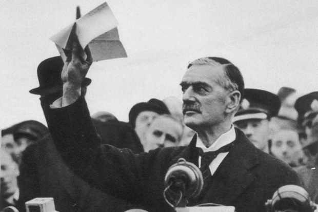 Neville Chamberlain holds aloft the famous piece of paper at Heston aerodrome on 30 September 1938. (Picture by Alamy)