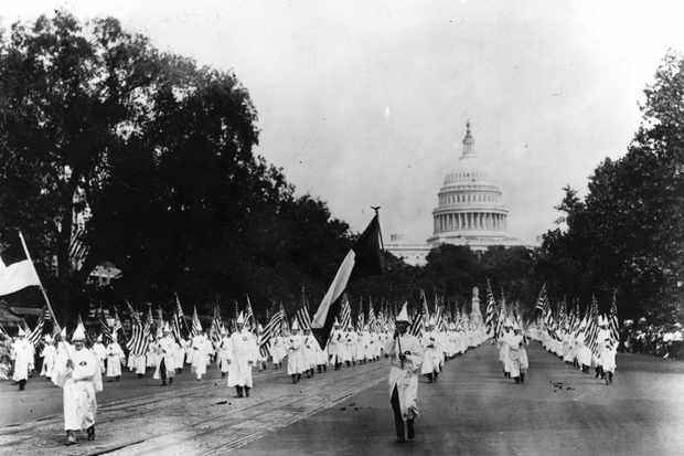 Members of the Ku Klux Klan march down Pennsylvania Avenue in Washington DC in 1925. The Klan of this era was a terrorist group in the precise meaning of that term, says Linda Gordon. (Photo by Topical Press Agency/Getty Images)
