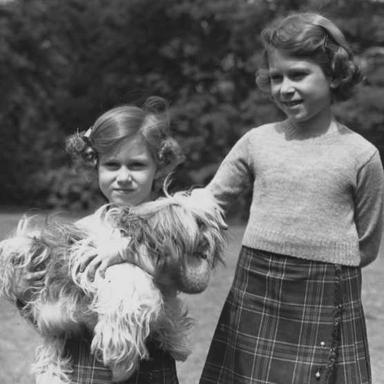 June 1936:  Queen Elizabeth II (as Princess Elizabeth) and her younger sister Princess Margaret (1930 - 2002) in the grounds of the Royal Lodge, Windsor.  Princess Margaret is holding one of their pet dogs, a Cairngorm terrier called Chu-Chu.  (Photo by Lisa Sheridan/Studio Lisa/Getty Images)